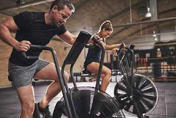 man and woman on bikes doing cardio